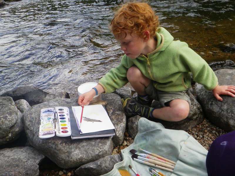 A boy paints with watercolours on the shore of the Magpie River