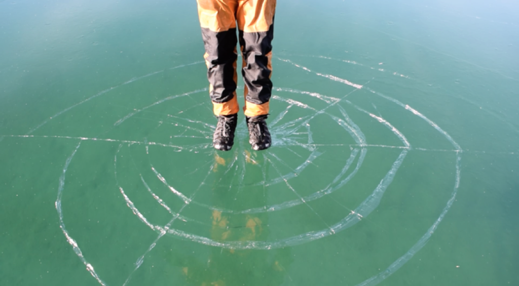 Person standing on ice that is cracking beneath them